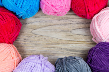Circled pastel colored yarn on the wooden table blank with blank space in the center.