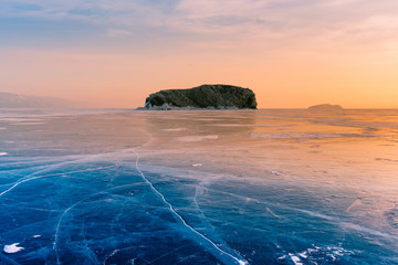 Rock on frozen water lake with sunset tone background, Baikal Russia