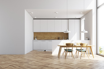 White and wooden kitchen with a table, wall