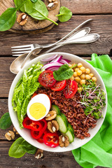 Buddha bowl dish with boiled egg, chickpea, fresh tomato, sweet pepper, cucumber, savoy cabbage, red onion, green sprouts, spinach leaves, walnuts, chia and rice. Healthy lunch, dinner. Detox diet