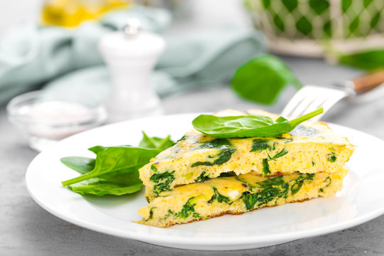 Omelet with spinach leaves. Omelette on plate, scrambled eggs