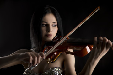 Portrait of sexy and beautiful woman playing on electric violin