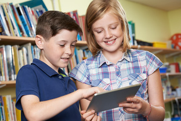 Pupils Using Digital Tablet In School Library