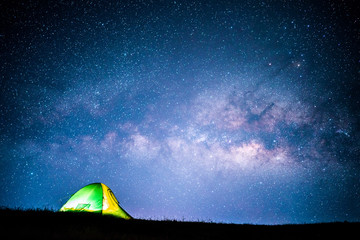 Milky way over green tent on hill.