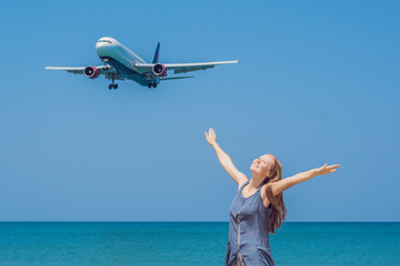 Young woman on the beach and landing planes. Travel concept
