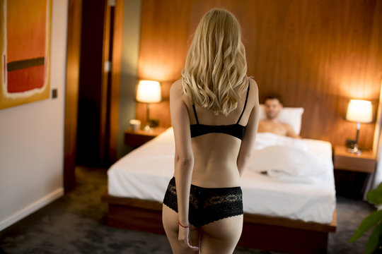 Young man is waiting for a sexy woman in bed