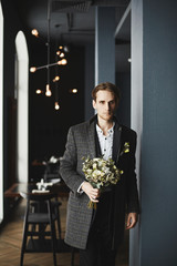 Handsome and stylish men in trendy plaid coat with bouquet of flowers
