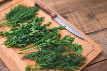 Dill and parsley on wooden table. Copy space