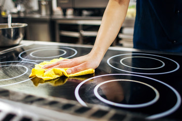 chef wipes the kitchen stove with a napkin
