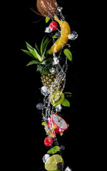 Wall Mural - Pieces of fruit in water splash, isolated on black background