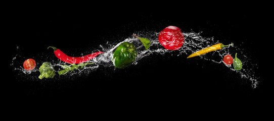 Mix of vegetable in water splash on black background.