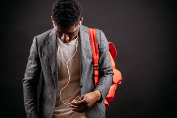close up image of black man in coat and T-shirt carring pink bagpack and choosing music to listen in the headphones. reel out earphones
