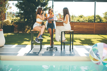 Young women drinking coctail and having fun by the pool