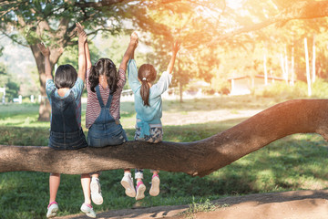 Children friendship concept with happy girl kids in the park having fun sitting under tree playing together enjoying good memory and moment of student friend lifestyle in school summer time day