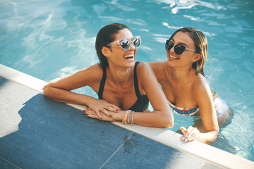 Young women having fun by the pool at  summer day