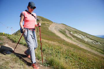 Photo of tourist girl walking with sticks and backpack on hill