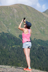 Photo of brunette photographing herself against of mountain