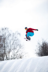 Picture of athlete in helmet riding snowboard from snow slope