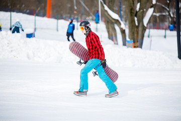 Photo of sporty man with snowboard walking on snowy resort