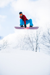 Photo of athlete with snowboard jumping in snowy resort