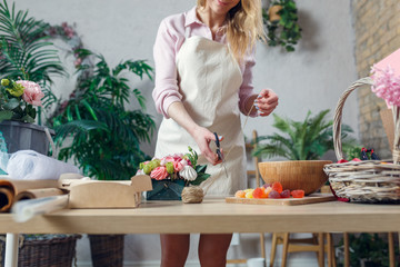 Photo of florist woman cutting scissor rope at table with bouquet, marmalade, marshmallow