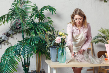 Image of florist woman cutting film at table with flowers, paper