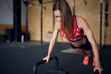 Image of young woman doing horizontal push-ups with bars