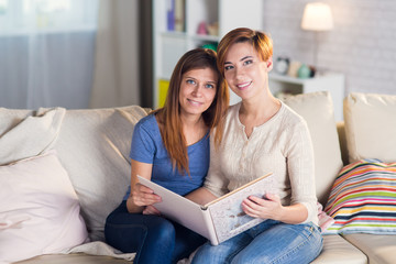 Homosexual couple of lesbian women at home on the couch watching a book