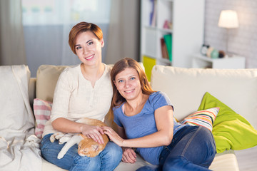 homosexual couple of lesbian women at home on the couch