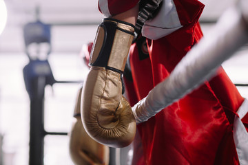 beaten boxer in yellow boxing gloves leaning on ropes. lost battle. without force. lost fight. defeat of an opponent