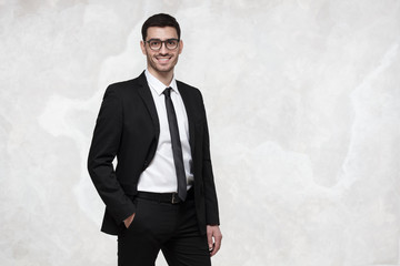Elegant smiling young business man standing against grey texture wall
