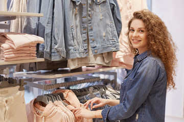 People, shopping, style, fashion and sale concept. Happy beautiful young female with curly hair, dressed in denim jacket, chooses outfit in clothing store, spends money on fashionable clothes