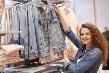 Horizontal shot of beautiful young woman with curly hair, pleased expression, chooses new denim jacket in clothing store, has satisfied look, being shopaholic. People, shopping, leisure concept