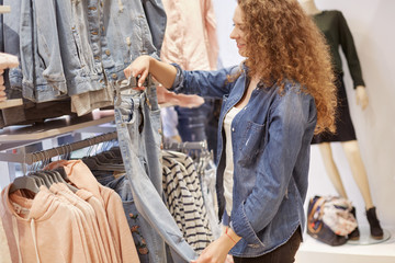 Cropped shot of curly woman in denim jacket, holds jeans on hangers, chooses new purchase for herself, poses in clothing store. Fashionable female buyer or shopper recieves pleasure from shopping