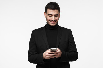 Young business man standing isolated on grey background looking attentively at screen of cellphone, browsing web pages and smiling nicely while chatting