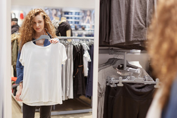 Shot of beautiful young female looks in mirror, going to try on white t shirt, stands in cloakroom, makes shopping in clothing store. Woman shopper spends money on new clothes. Buying concept