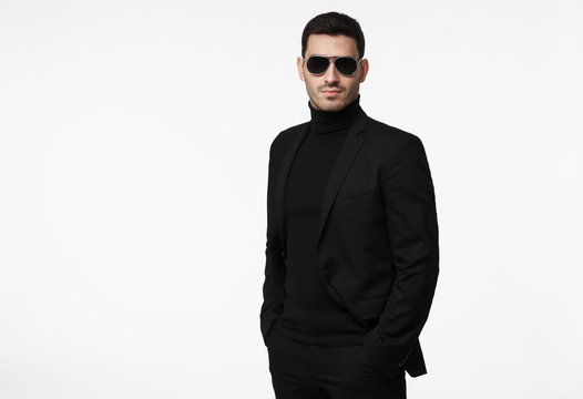 Serious body guard or secret agent wearing suit and sunglasses, isolated on grey background