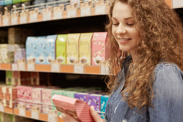 Horizontal portrait of deligted beautiful young female with curly hair reads with satisfied expression information about product, chooses something in supermarket. People and buying concept.