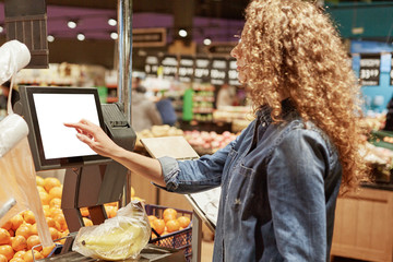 Back view of curly unrecognizable curly woman in denim jacket, weighs fruit products on electronic scales with touch screen, poses in supermarket, buys bananas. Now shopping in easier for you