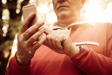 Close up of senior hand in park using mobile phone. Focus is on hands.