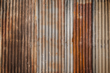 Rusty and corrugated iron metal construction site wall texture background with vignette.