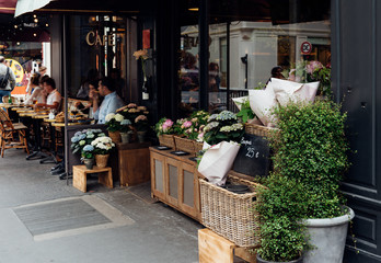 Cozy street with flower shop and table of  in Paris, France
