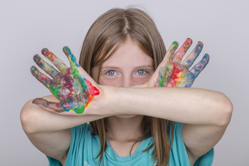 Portrait young girl and hands painted in colorful paints