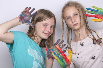Portrait two young girls and hands painted in colorful paints