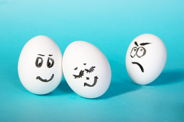the hen eggs with painted faces. The dissatisfied man looks at the happy couple. Jealousy. Blue background.