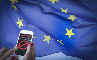 Female hands using a smartphone with geoblocking on screen and EU flag on the background. European Union Digital single market and regulation against Geo-blocking and geographically-based restrictions
