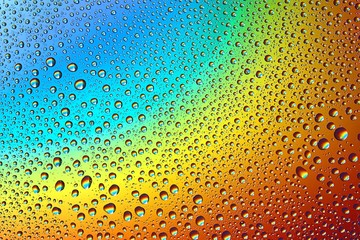 The colors of the rainbow on the wet glass. Reflection of colors in drops.