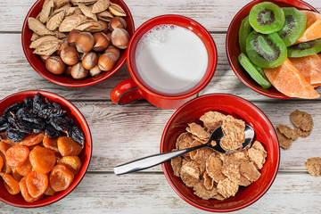 Still life with hazelnuts, dried apricots, mango, kiwi and raisins on wooden surface. Red mug with milk.