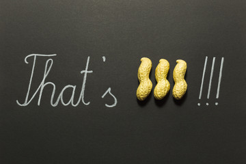 Concept of the saying that's peanuts! Raw unpeeled peanuts and white pencil hand writing on black paper background