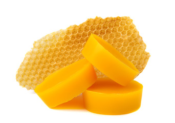 Yellow natural bee wax with a piece of honey cell on a white background.